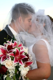 bride and groom kissing with wedding bouquet