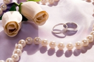 white roses, wedding rings and pearls
