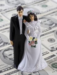 bride and groom figurine on stack of money