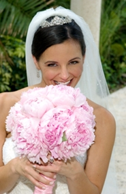 young bride smiling behind pink bridal bouquet
