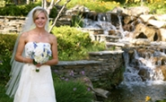 bride posing by waterfall