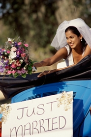 young bride with bouquet leaving reception with just married sign