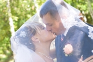young married couple kiss underneath wedding veil